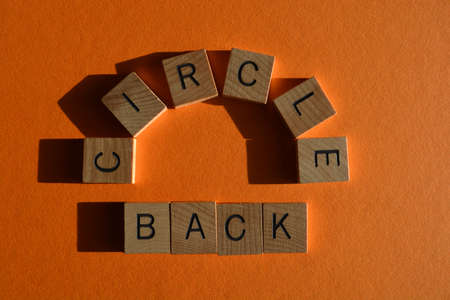 Circle Back, words in wooden letters isolated on orange background
