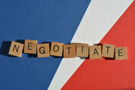 Negotiate, word in wooden alphabet letters isolated on red, white and blue background Banco de Imagens