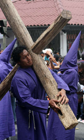 penitence: Quito, Ecuador, april 06, 2012 - Penitent bearing a cross at the Good Friday procession
