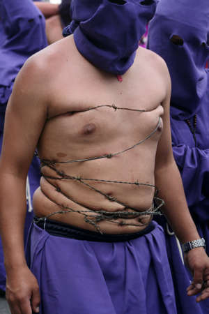 Quito, Ecuador - april 06, 2012 - Penitent with barbed wire at the Good Friday procession