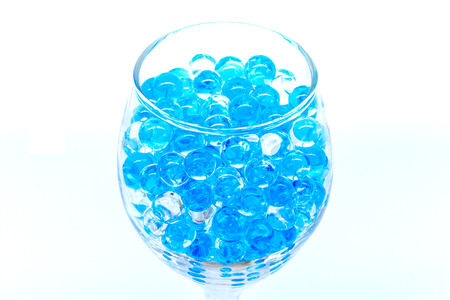 Polymer gel. Gel balls. balls of blue and transparent hydrogel, in glass bottle. Stock Photo