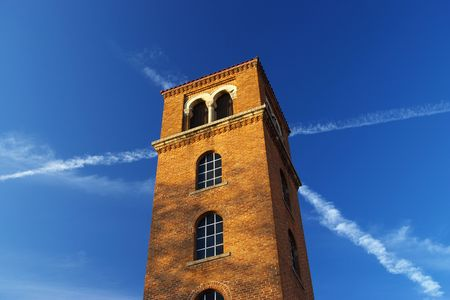 red brick tower against blue sky with contrails