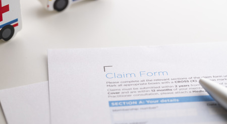 Insurance claim form with pen and mini model car Imagens