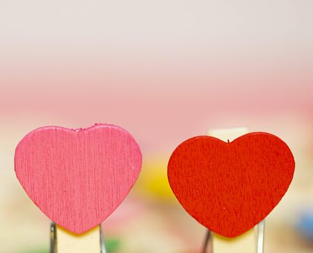 Two close up Beauty Colorful mini hearts with other color blur pink background and copy space