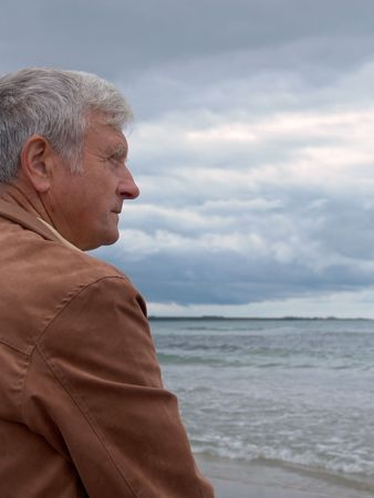 consideration: Elderly man looking out on the ocean
