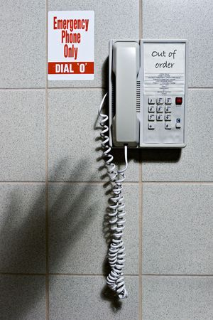 out of order: Shadow of hand reaching for out of order emergency phone Stock Photo