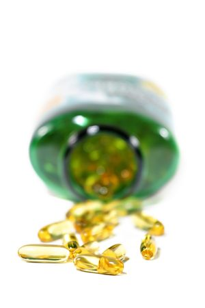 cod oil: Cod liver oil pills spilling from a bottle Stock Photo