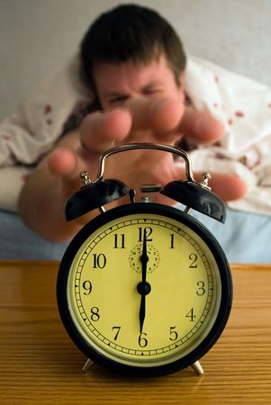 Tired man reaching for alarm clock at 6:00 in the morning