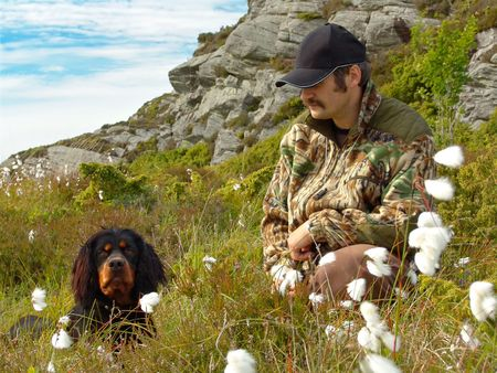 A hunter and his Gordon Setter in cotton grass Stock Photo