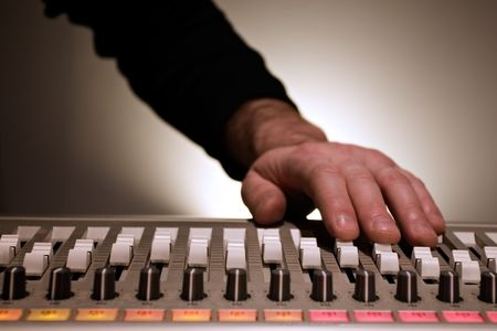 Hand adjusting sliders on a mixing board
