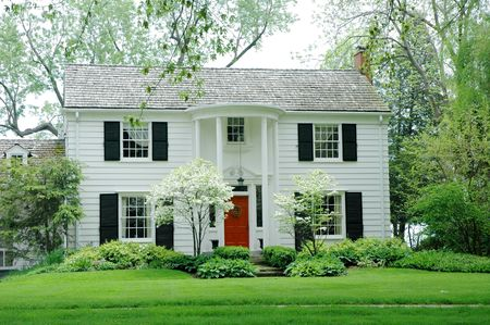 White formal house with siding, black shutters and bright green, manicured lawn  garden Stock Photo
