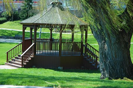 gazebo: Gazebo in park with large willow tree and spring green grass