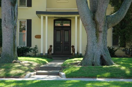 House entrance to cream stucco home with pathway, large trees, pillars and dog statues Banque d'images