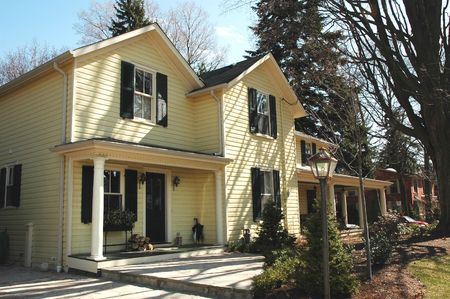Yellow house with black shutters, siding and porch Stock Photo - 449583