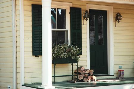 Front house / home entrance with rubber boots, stack of wood, planter, lantern and black shutters and door Stock Photo - 449579