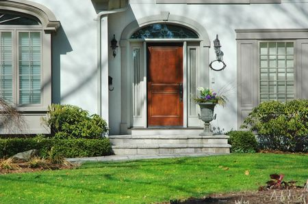 Front entrance of home with flower urn and wood door Stock Photo - 449584