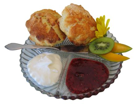 Cream, jam and scones with kiwi, melon and pretty flower photo