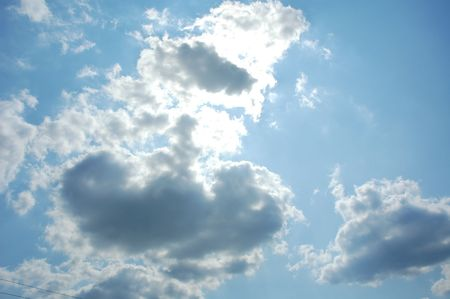 Bright blue sky with sun behind cloud