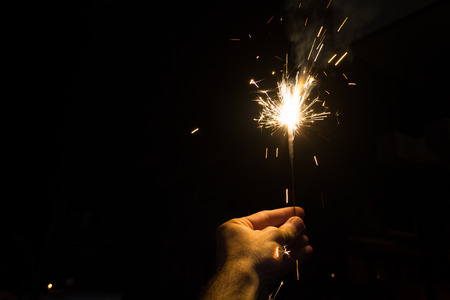 Hand holding a sparkler at night
