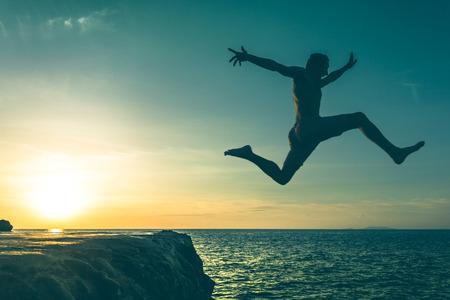 일몰, 태국에서 Koh Phangan 섬에 바다로 절벽을 통해 점프하는 사람 (남자). 빈티지 효과입니다. 스톡 콘텐츠