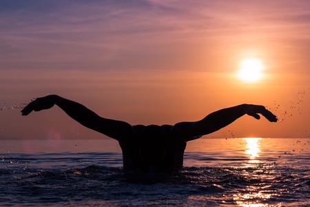 humilde: La silueta del hombre sin la cabeza y los brazos abre la técnica de la mariposa del movimiento de natación en la puesta del sol asombrosa en la playa en la isla de Koh Phangan, Tailandia. Bengala de lente solar