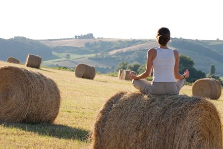 pranayama: Woman practicing yoga in a field