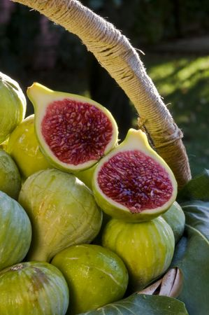 set of figs on fig tree leaves in a old basket