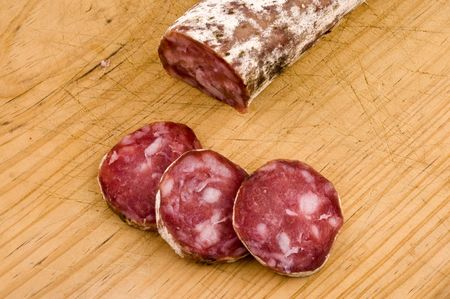 Iberian salami slices cut on wooden board
