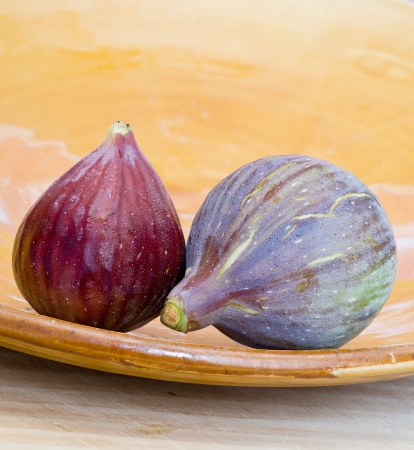 Two figs on terracotta dish Stock Photo
