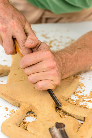 sculptor: Hands of a sculptor using a chisel on a wood carving Editorial