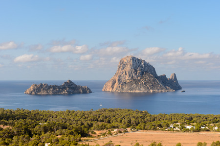 Es Vedrà ( is a small rocky island of the south western seaboard of the Spanish island of Ibiza.] The island, which has 413 meters of height, is part of the Cala d'Hort nature reserve and lies 1.5423 miles of the coast at Cala d'Hort, which is in the Stock Photo