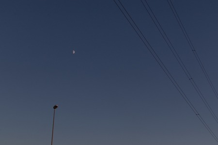 Telephone wires, street lamp and moon in the background