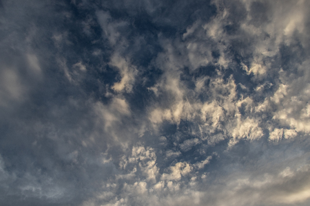 Fluffy clouds background over blue sky with sunlight