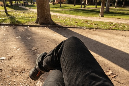 First person view of a man legs with jeans shorts and boots sitting on a bench in a public park Stock Photo