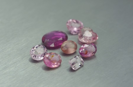 Group of pink and purple gemstones on metal surface