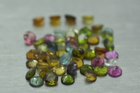 Group of precious stones of different colors and shapes on metal surface