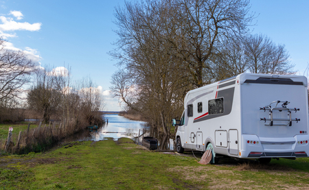 Camper in front of a beautiful natural landscape with a lake on sunny day