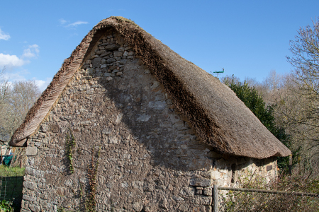 Old stone house with thatched roof on rural place of the french brittany