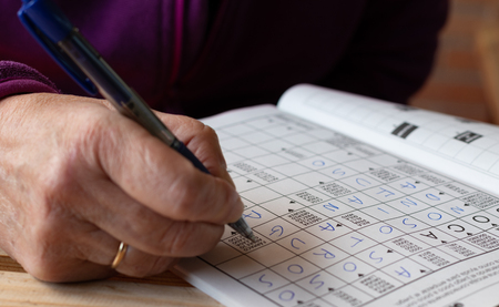 Hand of senior woman with a ring doing crosswords puzzles in a notebook. Leisure and free time Stock Photo