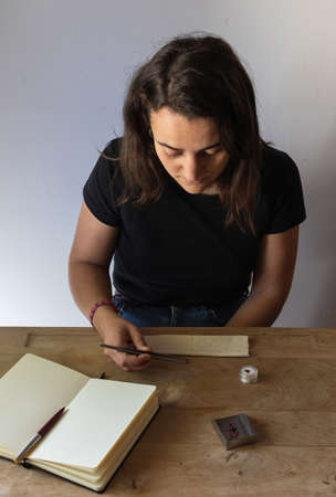 Female gemologist working observing precious stones in her workspace. Wooden table with notebook, suede, shovel and gems Banco de Imagens