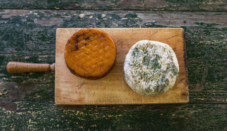 Top view of two cheeses on a wooden board on a rustic table. Smoked cheese and moldy blue cheese.
