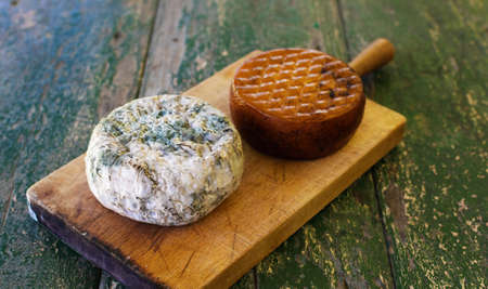 Two cheeses on a wooden board on a rustic table. Smoked cheese and moldy blue cheese.
