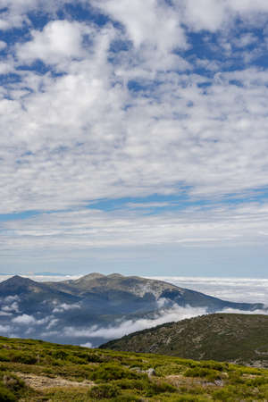 Beautiful sea of clouds from a mountain on a sunny day. Low clouds in the Sierra de Guadarrama, Madrid.