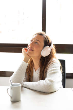 Happy and relaxed woman uses her wireless headphones at home leaning on the table where there is a cup Reklamní fotografie