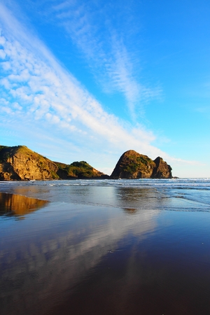 живописный закат на пляже Пиха с скальными образованиями на заднем плане Фото со стока