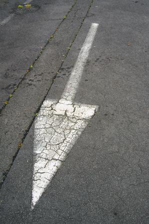 white arrow symbol on black asphalt road