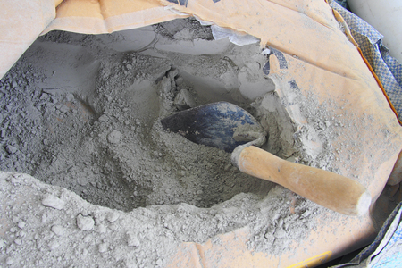 close up trowel in a bag of cement powder Standard-Bild