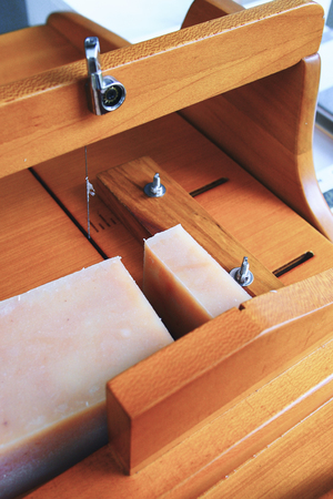 Close up cutting homemade soap with a wooden cutter