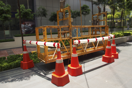 A scaffold elevator cordoned with cone barriers
