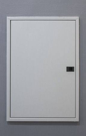 domestic fusebox on grey wall Stock Photo